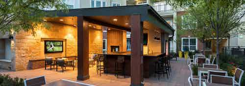 Nighttime view of cabana at AMLI Frisco Crossing apartments with serving bar and surrounding tables and chairs