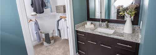 Interior view of AMLI Joya apartment bathroom with single sink vanity, granite counters, mirror, and walk-in closet