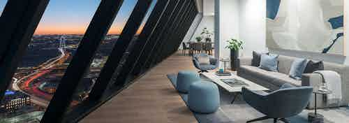 Penthouse living room at night with floor to ceiling  windows sloped over couch and 2 chairs at AMLI Fountain Place apartments