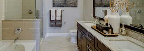 AMLI River North bathroom with a toilet and double vanity along one wall and seperate bathtub and shower along another