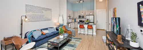 Interior of AMLI Decatur apartment living room with colorful furniture and light wood floors leading to island kitchen