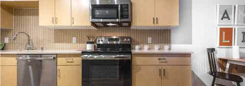 Interior view of an AMLI Wallingford apartment kitchen with light cabinets white quartz counter tops and stainless steel appliances