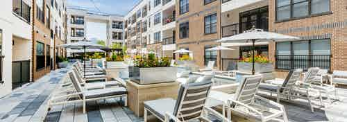 Cooling spa at AMLI Quadrangle apartments with a gray lounge seating shaded by gray umbrellas and flowers in metal planters
