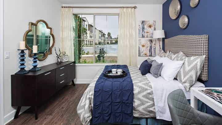 Interior view of AMLI Spanish Hills bedroom with patterned queen upholstered headboard, dresser and window with curtains