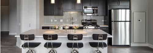 Interior view of an AMLI Lofts kitchen with dark wooden cabinets and a quartz island with four black bar stools