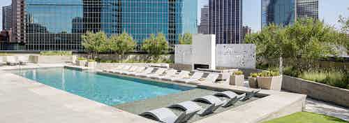 AMLI at Fountain Place landscaped rooftop swimming pool surrounded by lounge chairs on 3 sides and large office buildings