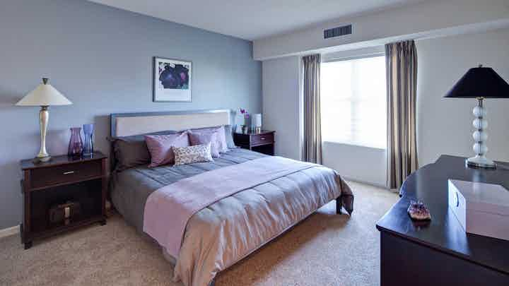 AMLI at Seven Bridges bedroom with grey decor and pink accents featuring a large bright window with flowing curtains