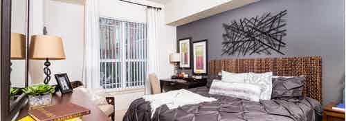 Interior of a bedroom at AMLI Park Avenue apartments with a dark gray bed spread and a wicker head board and a window view