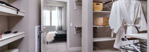 Interior of AMLI Littleton Village apartment's large closet with shelving, hanging bath robes and peek into master bedroom