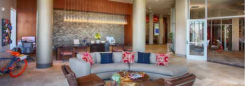 Interior view of the lobby at AMLI Denargo Market apartments with couches and chairs and a staff desk with hanging lights