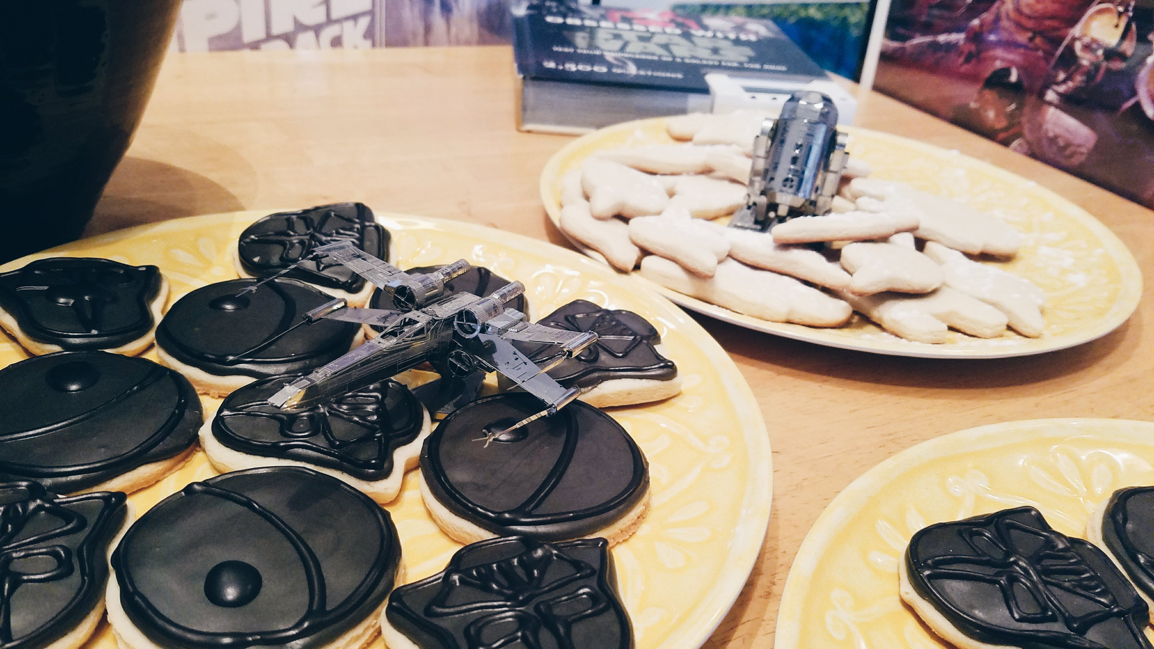 Metal model of an X-Wing starfighter next to a plate of Darth Vader cookies