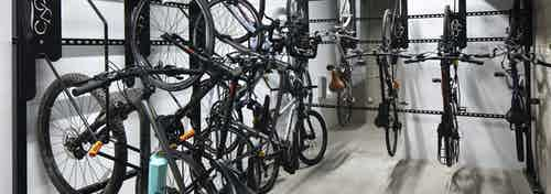 Interior view of the private bicycle storage room at AMLI Park Broadway apartment building with multiple hanging racks
