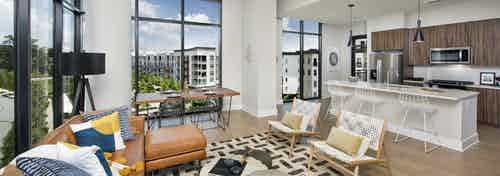 AMLI Lenox apartment interior with large windows and brown sofa with colorful pillows and dining area and island kitchen