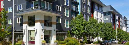 Exterior of AMLI 535 apartment building with retail and lushes Trees and bushes with side walk