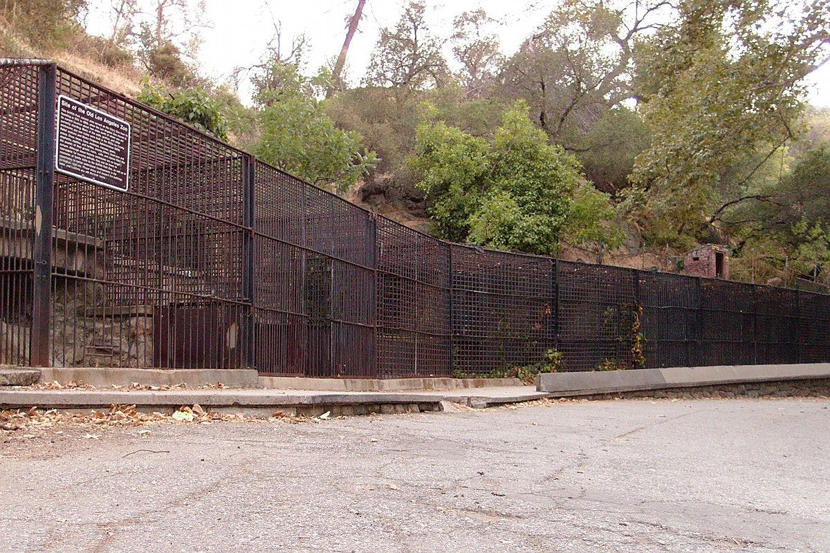 Old metal animal cages attached to rocky walls