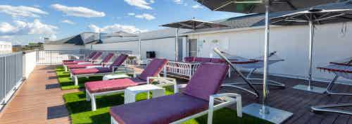 Exterior view of roof deck at AMLI South Shore with purple lounge chairs overlooking scenic view with a blue cloudy sky