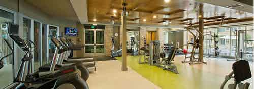 Interior view of AMLI RidgeGate fitness center with flat screen TV, cardio equipment and free weights facing courtyard