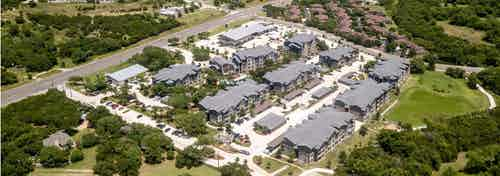 Daytime aerial view of AMLI Covered Bridge apartment community complex, retail buildings and parking areas