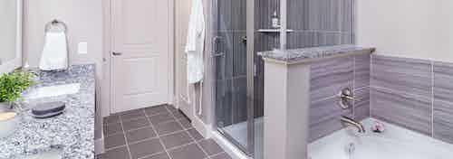 Interior of AMLI Littleton Village apartment bathroom with granite countertops double vanity, soaking tub and walk-in shower