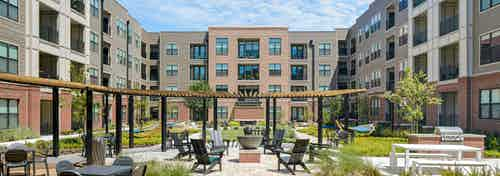 AMLI Addison courtyard with firepit at center surrounded by Adirondack chairs with grill and hammocks and other seating