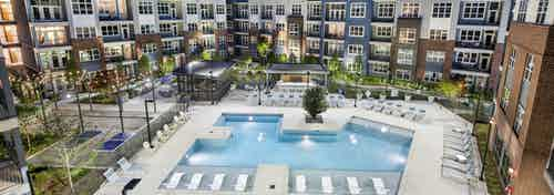 Overhead evening view of AMLI Decatur landscaped pool area with hanging lights and lounge chairs and uplit colorful building