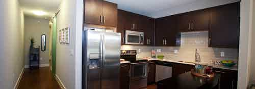 A kitchen at AMLI Riverfront Park apartments with stainless steel appliances and cupboards and a view of the front door