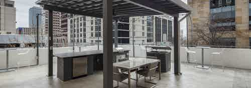 AMLI Downtown covered rooftop grill area with a steel grill and various outdoor seating surrounded by Austin skyscrapers