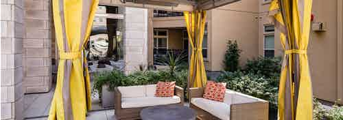 Daytime view of curtained cabana with outdoor lounge sofas and decorative orange accent pillows at AMLI RidgeGate apartments