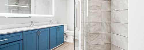 Bathroom at AMLI 535 with a stand up shower and double sink vanity with blue cabinets and large mirror above