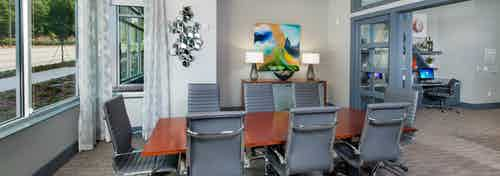 Conference room at AMLI Piedmont Heights apartment building with wood table and eight office chairs with artwork on walls