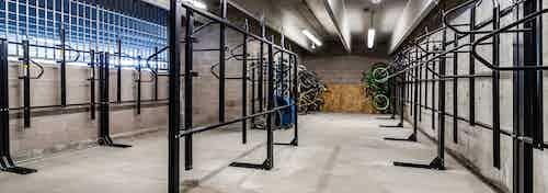 Interior of AMLI Littleton Village apartment building bike/ski/snowboard storage room with brick walls and ample bike racks
