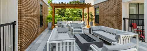 AMLI Quadrangle shaded courtyard fire pit area with gray cushion seating and a wood pergola with lush greenery in the back