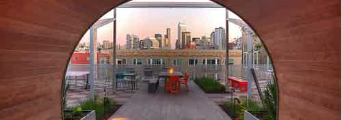 View of Downtown Seattle from the AMLI South Lake Union rooftop with fire pit lush landscape and seating