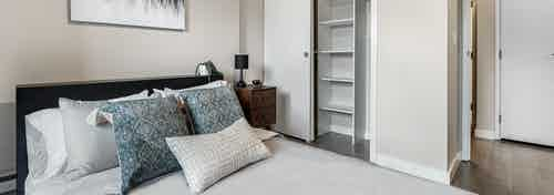 AMLI Bellevue Park bedroom with queen bed with light grey bedding and brown nightstand and white closet with built ins