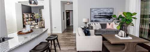 An apartment living room at AMLI Joya with cool neutral colors, a couch and coffee table and kitchen island with stools