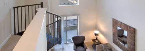 Interior view of AMLI Warner Center apartment loft's upper level facing down to furnished living room area with framed mirror