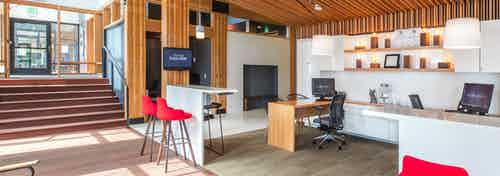 The leasing office at AMLI Wallingford with high ceilings seating bright walls and lots of natural wood on stairs floor and ceiling