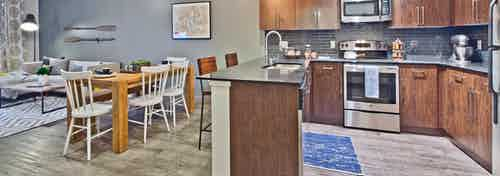 Interior view of AMLI Mark24 apartment kitchen with dark cabinets black quartz counter tops light laminate floors and view of living room