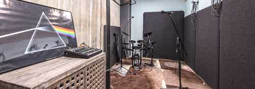 Interior music room of AMLI Arc with music soundboard microphones small electric drum set and sound proof room