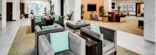 A resident lounge at AMLI Cherry Creek apartments with gray padded chairs with mint colored pillows and other seating areas