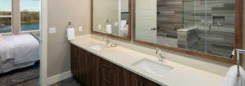 Close up of double vanity sink at AMLI South Shore with white countertops and dark wood cabinets and a peek into bedroom