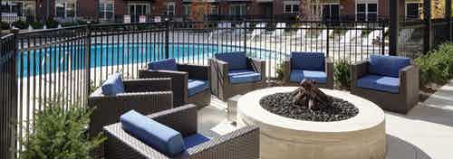 Exterior of courtyard at AMLI Deerfield with closeup of firepit and a swimming pool in background with  lounge chairs