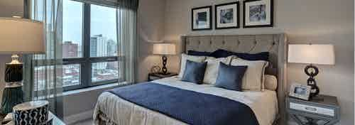 Bedroom at AMLI River North with beige walls and white bedding with dark blue accents beside a window with daytime views