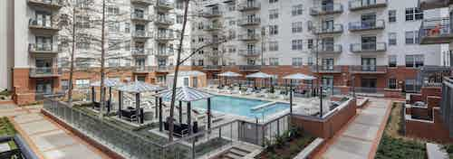 Aerial view of AMLI Downtown apartment building courtyard pool surrounded by cabanas and lounge seating and lush landscaping