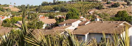 Daytime aerial view above AMLI Spanish Hills apartment community capturing the outside hills and lush greenery of Camarillo