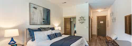 Interior view of AMLI Parkside bedroom with light hardwood and cream walls with blue decor and a peek into walk in closet