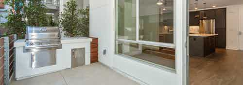 Daytime exterior view of private patio with BBQ grill facing into kitchen area at AMLI Park Broadway apartment building