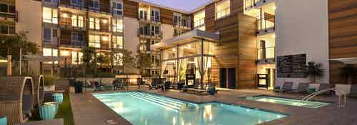 Evening view of AMLI Marina Del Rey landscaped and lit swimming pool area with lounge seating, jacuzzi and entertaining lanai