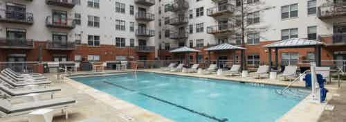 AMLI Downtown courtyard resort style pool surrounded by gray lounge chairs with small white tables and cabanas