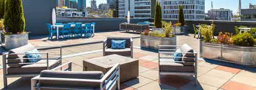 Daytime view of AMLI 535 apartment building rooftop deck with patio furniture fire pit bushes and view of Space Needle and downtown Seattle